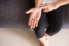 Mani anziane della donna che controllano il suo impulso con due dita sul polso immagini stock libere da diritti