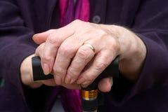 Mani anziane sul bastone da passeggio Fotografia Stock