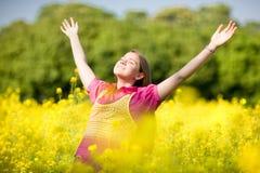 Mani aperte teenager di sorriso che si levano in piedi sul campo giallo Fotografia Stock