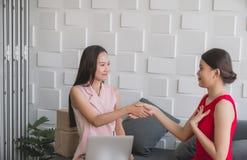 Mani asiatiche suscessful di scossa del proprietario della donna di piccola impresa belle e lavorare a casa ufficio, busin online fotografie stock libere da diritti