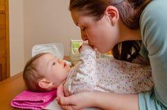 Mani bacianti della madre della sua menzogne del bambino Fotografia Stock