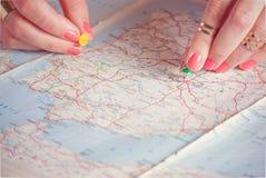 Mani che appuntano i punti di destinazione di viaggio sulla mappa, filtrata Fotografia Stock Libera da Diritti