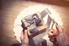 Mani che aprono regalo Immagini Stock