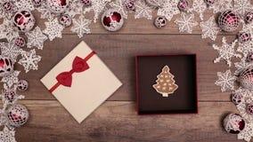 Mani che aprono regalo di Natale che contiene un biscotto del pan di zenzero stock footage