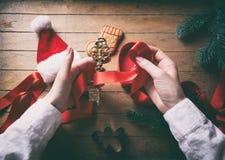 Mani che avvolgono chiave dorata ed i regali di natale Fotografie Stock Libere da Diritti