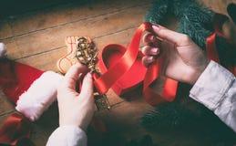 Mani che avvolgono chiave dorata ed i regali di natale Fotografie Stock