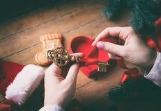 Mani che avvolgono chiave dorata ed i regali di natale Fotografia Stock Libera da Diritti