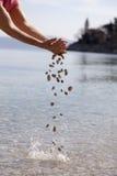 Mani che cadono le piccole pietre nel mare immagine stock libera da diritti