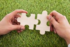 Mani che collegano due pezzi di puzzle Fotografie Stock Libere da Diritti