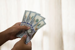 Mani che contano i dollari Immagine Stock