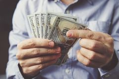 Mani che contano le banconote del dollaro su superficie di legno scura immagine stock