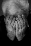 Mani che coprono fronte dell'uomo anziano Fotografie Stock