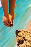 Mani che costruiscono il castello della sabbia Immagini Stock Libere da Diritti