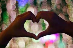Mani che creano cuore contro Bokeh Fotografia Stock Libera da Diritti