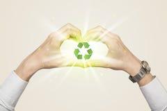 Mani che creano una forma con il riciclaggio del segno Immagine Stock