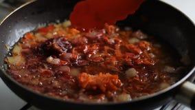 Mani che cucinano cipolla fritta con la carota in pentola archivi video