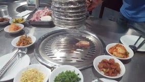 Mani che cucinano per un gruppo di amici per mangiare barbecue archivi video