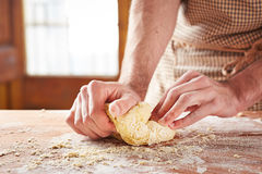 Mani che cuociono pasta sulla tavola di legno Fotografia Stock