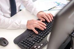 Mani che digitano su una tastiera Fotografie Stock