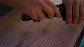 Mani che disfanno la copertura di grande coltello per aprire le bottiglie archivi video