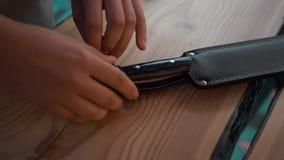 Mani che disfanno la copertura di grande coltello per aprire le bottiglie video d archivio