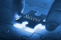 Mani che dispongono ultima parte di un puzzle fotografia stock libera da diritti