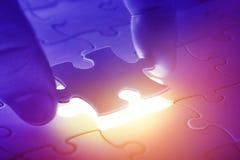 Mani che dispongono ultima parte di un puzzle immagini stock
