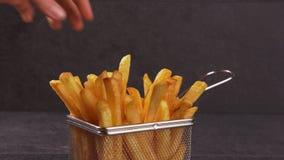 Mani che dividono le patate fritte deliziose dal canestro stock footage