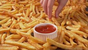 Mani che dividono le patate fritte deliziose servite su un grande piatto stock footage