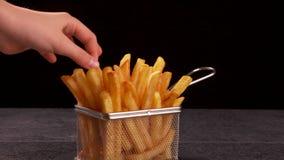 Mani che dividono le patate fritte deliziose servite in un piccolo canestro di frittura video d archivio