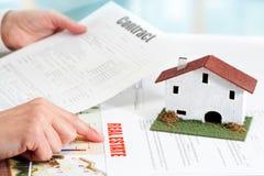 Mani che esaminano i documenti della proprietà del bene immobile. Fotografia Stock Libera da Diritti