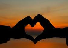 Mani che fanno figura del cuore Fotografie Stock