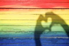 Mani che fanno l'ombra del cuore di amore sul fondo dell'arcobaleno