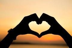 Mani che formano una figura del cuore Fotografie Stock