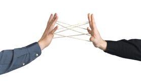 Mani che giocano con la corda, simbolizzante connettività, amicizia, forti obbligazioni fotografia stock