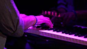 Mani che giocano la luce di concerto del piano stock footage
