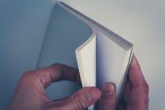 Mani che girano le pagine in libro vuoto con le pagine in bianco Immagine Stock Libera da Diritti