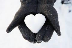Mani che giudicano cuore fatto da neve immagine stock libera da diritti