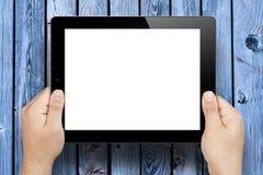 Mani che giudicano il pc della compressa dello schermo in bianco di legno Fotografie Stock