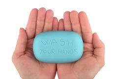 Mani che giudicano la barra blu del sapone con lavaggio le vostre mani scritta Fotografia Stock Libera da Diritti