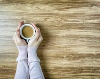 Mani che giudicano le tazze di caffè calde sulla tavola di legno Immagine Stock