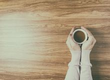 Mani che giudicano le tazze di caffè calde sulla tavola di legno Immagini Stock