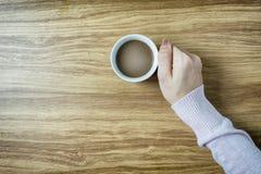 Mani che giudicano le tazze di caffè calde sulla tavola di legno Fotografia Stock Libera da Diritti
