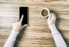 Mani che giudicano le tazze di caffè calde sulla tavola di legno Immagine Stock Libera da Diritti