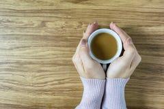 Mani che giudicano le tazze di caffè calde sulla tavola di legno Fotografie Stock