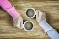 Mani che giudicano le tazze di caffè calde sulla tavola di legno Fotografia Stock