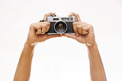 Mani che giudicano una macchina fotografica di Wintage isolata su bianco fotografia stock libera da diritti