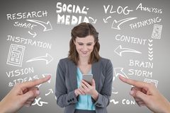 Mani che indicano alla donna felice di affari che per mezzo del suo telefono contro il fondo grigio con il ico sociale di media Immagini Stock Libere da Diritti