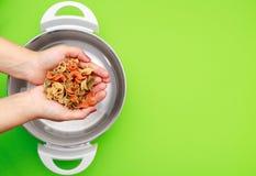 Mani che inseriscono pasta di verdure variopinta al vaso della cucina sul fondo piano verde del raggio fotografie stock