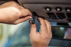 Mani che installano piccola esposizione in automobile fotografie stock